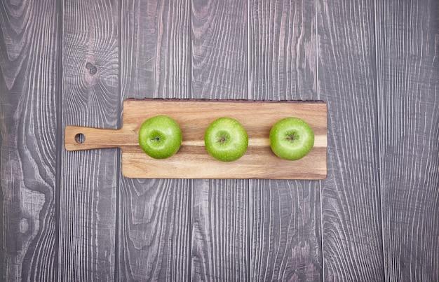 Вид сверху зеленых яблок на деревянной доске