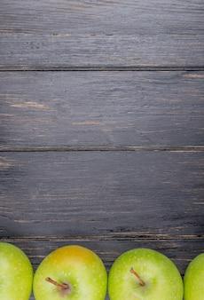 Вид сверху зеленых яблок на деревянном фоне с копией пространства