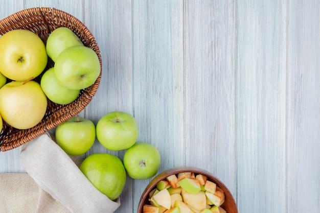 Вид сверху зеленых яблок, разлив из мешка и корзина яблок с миской кубиков яблок на деревянный стол с копией пространства