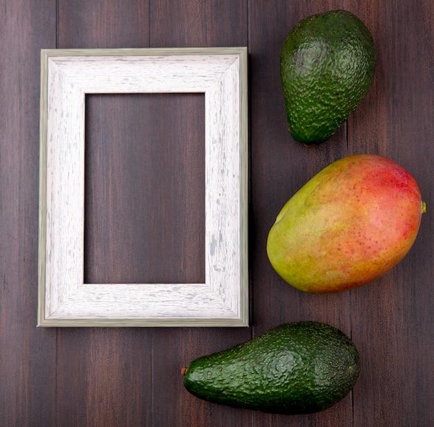 木製の表面にマンゴーと緑のアボカドのトップビュー