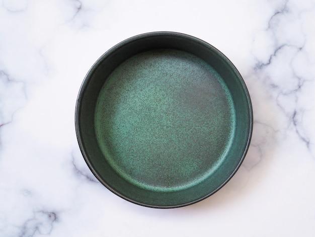 緑のセラミックプレートの平面図は、タイル、陶器のボウル、白い大理石のテーブルに分離された空の皿です。