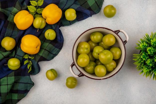 新鮮な桃と白い背景のチェックされた布で分離されたチェリープラムのボウルに緑のチェリープラムのトップビュー