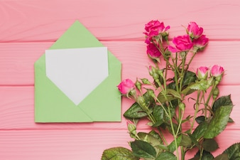 Top view of green envelope with blank note and flowers