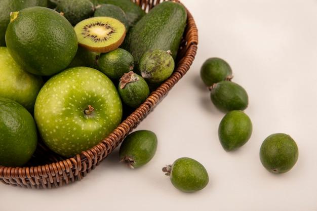 Вид сверху зеленых фруктов, таких как яблоки, авокадо, лаймы и фейхоа, на ведре на белой стене