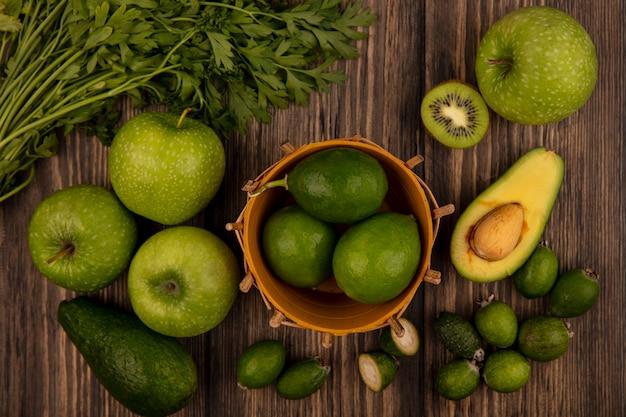 木製の壁に分離されたリンゴキウイフェイジョアアボカドとパセリとバケツの上の緑のライムの上面図