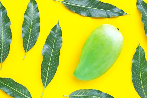 Вид сверху зеленого манго с листьями на желтом столе. вид сверху