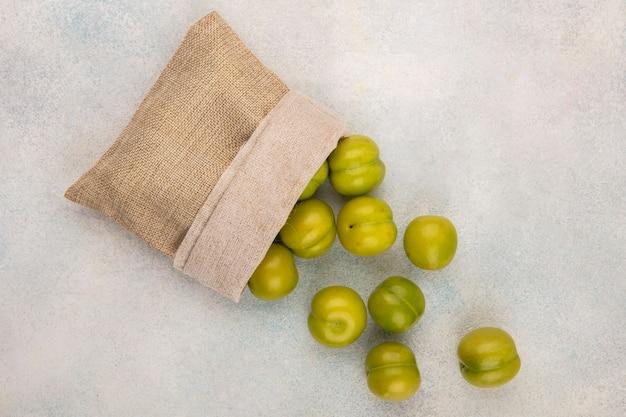 白い背景の上の袋からこぼれる緑の梅のトップビュー