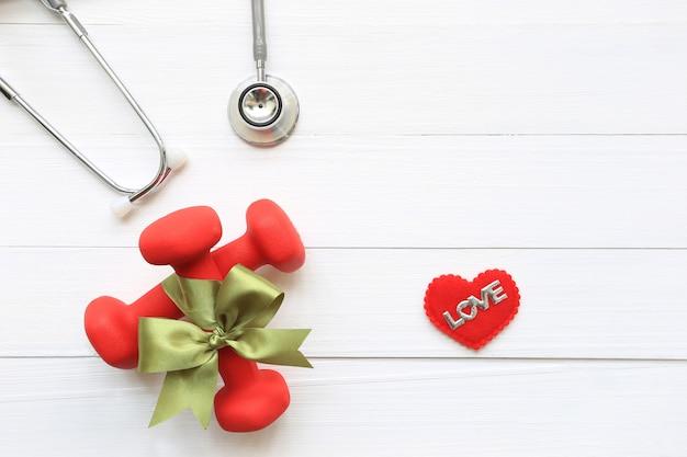 Взгляд сверху зеленой ленты с гантелями и стетоскопом здорового сердца на деревянной белой предпосылке