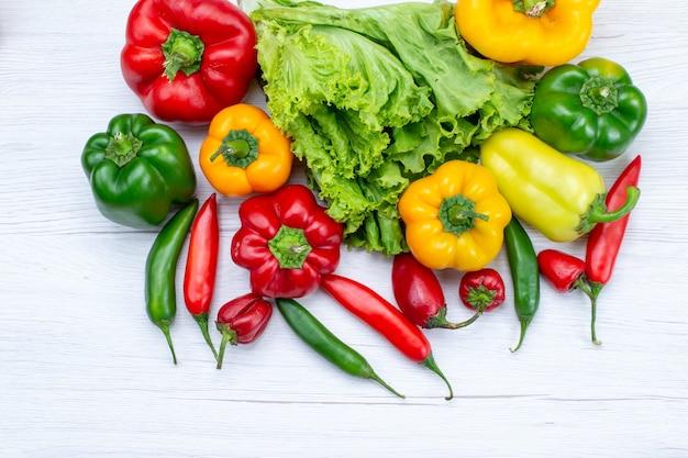 白い机の上にフルピーマンとスパイシーペッパー、野菜料理の食事の材料と一緒にグリーンサラダの上面図