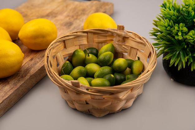 회색 배경에 나무 주방 보드에 레몬 양동이에 녹색 피부 kinkans의 상위 뷰