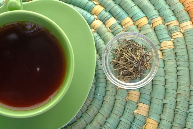 테이블에 작은 유리 그릇에 녹차와 허브 잎의 상위 뷰