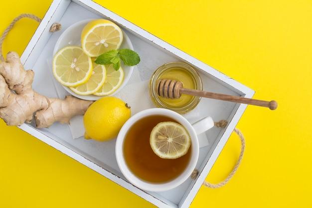 Вид сверху зеленого чая с лимоном, медом и имбирем в белом деревянном подносе на желтом