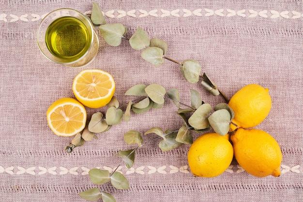 Вид сверху зеленого чая с лимонами на коричневой скатерти.