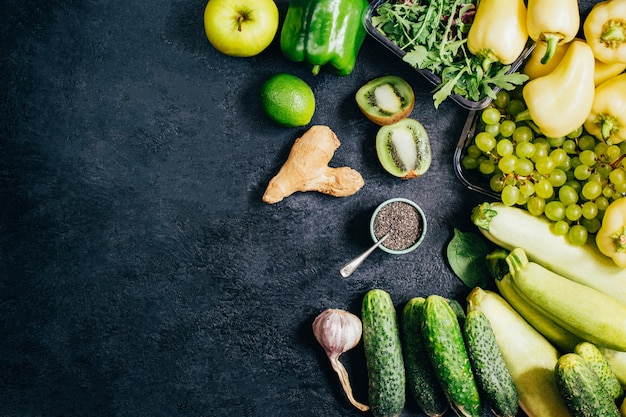 テキスト用の空き領域と黒の背景に緑の野菜や果物の上面図