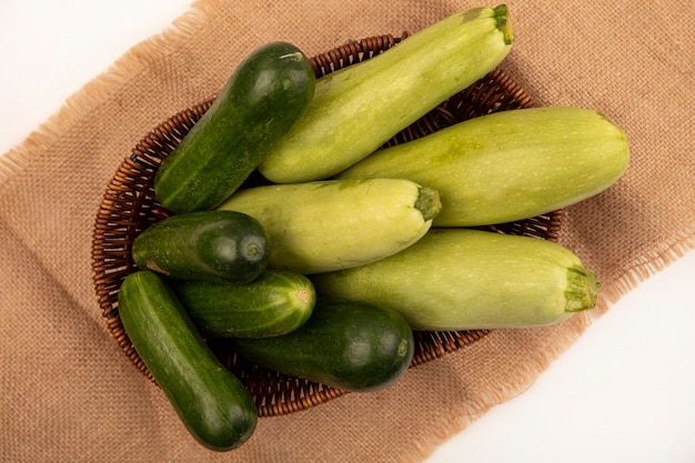 Вид сверху зеленых овощей, таких как огурцы, цуккини, на ведре на мешковине на белой стене