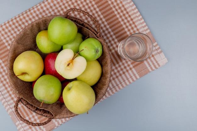 Вид сверху зеленых желтых красных яблок в корзине и стакане воды на клетчатой ткани и сером фоне