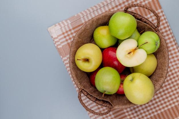 Вид сверху зеленых желтых красных яблок в корзине на клетчатой ткани и сером фоне с копией пространства