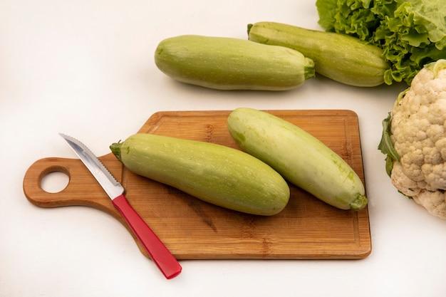Вид сверху зеленых цукини на деревянной кухонной доске с ножом с салатом и цветной капустой, изолированными на белой стене