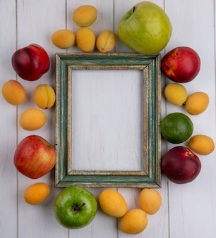 白い表面に桃のリンゴとアプリコットと緑がかった黄色のフレームのトップビュー