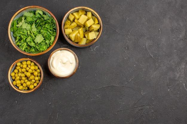 Вид сверху зелени и фасоли с солеными огурцами на серой поверхности