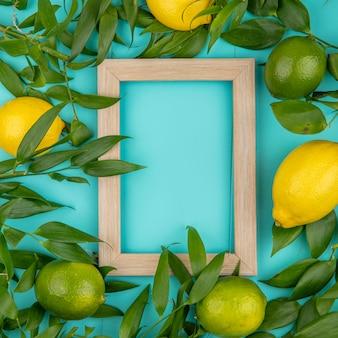 Вид сверху зеленых и желтых лимонов с листьями на синей поверхности