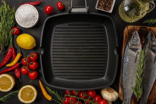 Вид сверху на сковороду-гриль с сибасом, розмарином и овощами