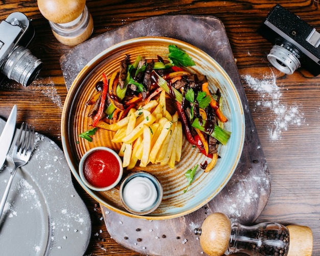 야채와 구운 쇠고기 고기의 상위 뷰 접시에 감자 튀김과 소스와 함께 제공