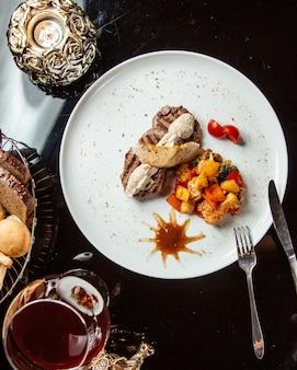Вид сверху на гриле говяжий медальон с соусом и овощами на белой тарелке на столе