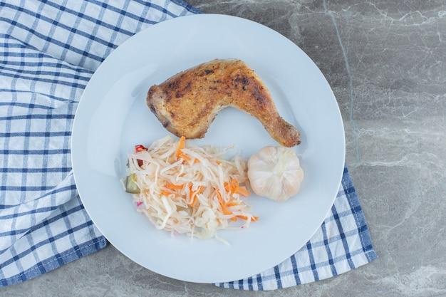 Вид сверху жареной курицы и квашеной капусты на белой тарелке.