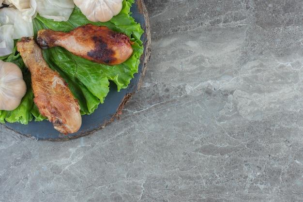 Вид сверху жареной куриной голени на листьях салата.