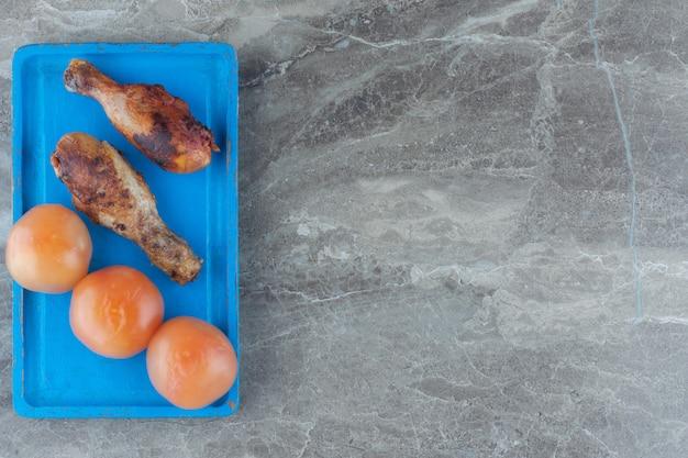 Вид сверху жареной куриной ножки и томатного огурца на синей деревянной тарелке.
