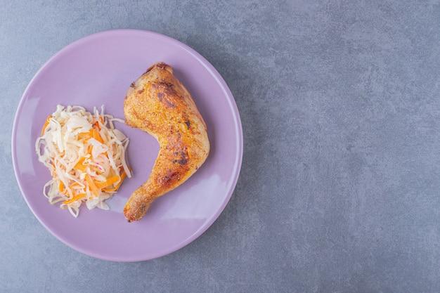 Вид сверху куриной ножки-гриль с кучей квашеной капусты на фиолетовой тарелке.