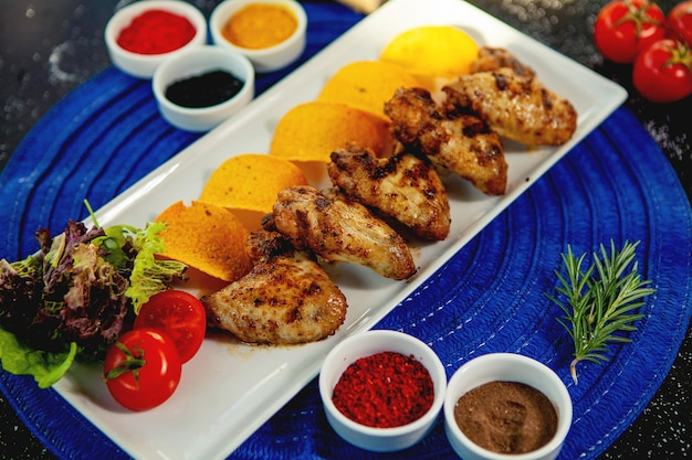 구운 닭 날개의 평면도는 튀긴 감자와 신선한 샐러드와 함께 제공