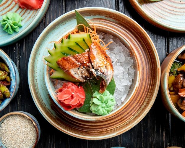 Вид сверху жареного японского угря с нарезанными огурцами и имбирем, подается с соусом васаби на листе бамбука и на кубиках льда в тарелке на столе