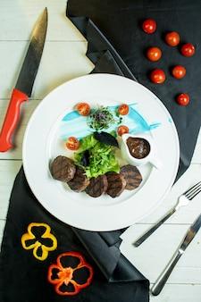 Вид сверху на гриле медальоны из говядины с помидорами черри и соусом на тарелке