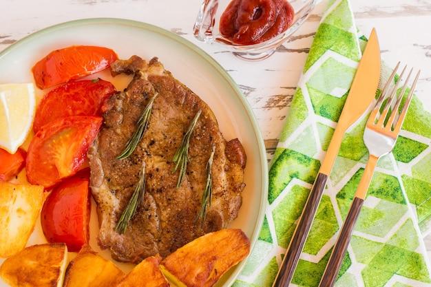 Вид сверху на зажаренную свиную шею, которую подают с жареным картофелем, помидорами и cetcup на светлом фоне.