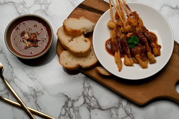 구운 돼지 고기 satay (moo satay)의 평면도는 대리석 식탁에 땅콩 소스와 구운 빵 제공