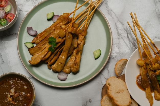 오이를 곁들인 구운 돼지 고기 satay (moo satay)의 평면도는 대리석 책상에 땅콩 소스와 구운 빵과 함께 제공됩니다.