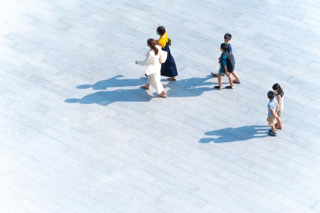 Вид сверху группы семейных матерей и детей, идущих по пешеходной дорожке на открытом воздухе