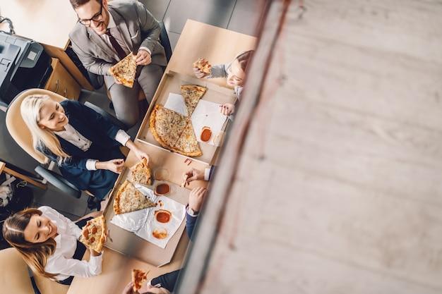 Вид сверху группы деловых людей, сидящих за столом, едят пиццу на обед и болтают.