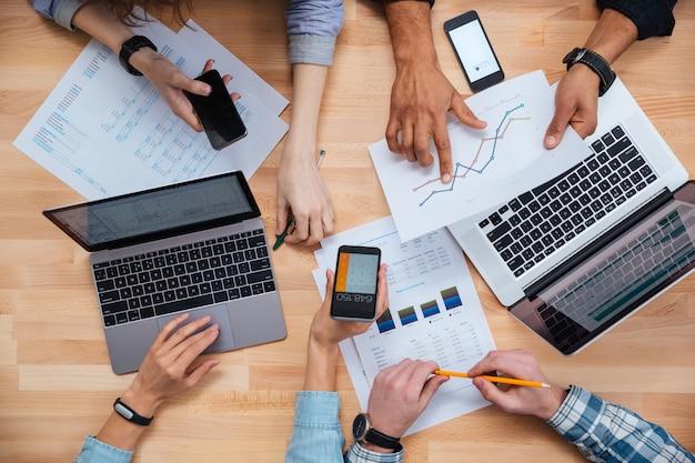 携帯電話やラップトップを使用し、財務報告のために働いているビジネスマンのグループの上面図