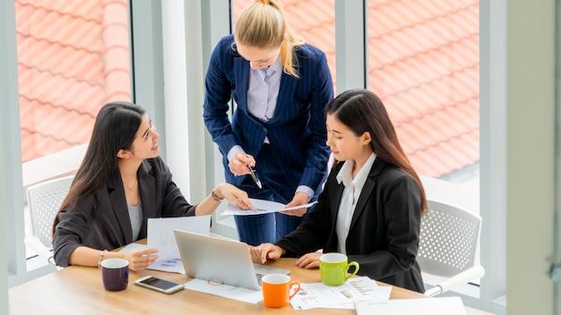 会議中に議論している多民族の幹部のグループの上面図。オフィスでテーブルの周りに座って笑顔のビジネス女性。
