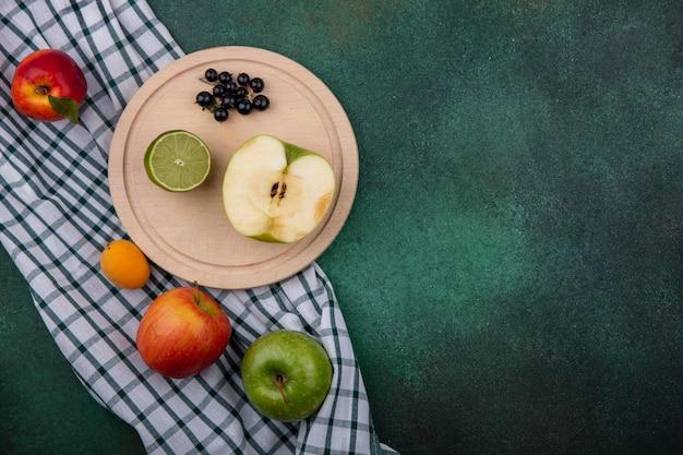 スタンドにライムと黒スグリと緑の表面に市松模様のタオルに桃と半分青リンゴの平面図