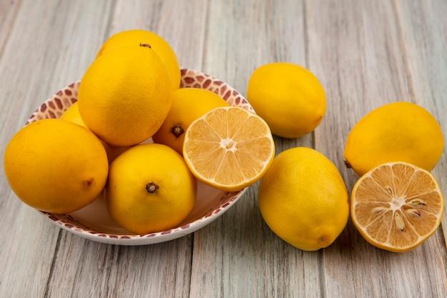 Вид сверху на половину и целые лимоны на миске с лимонами, изолированными на серой деревянной стене