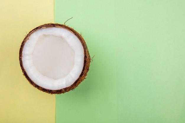 Вид сверху половинки кокоса на желто-зеленой поверхности