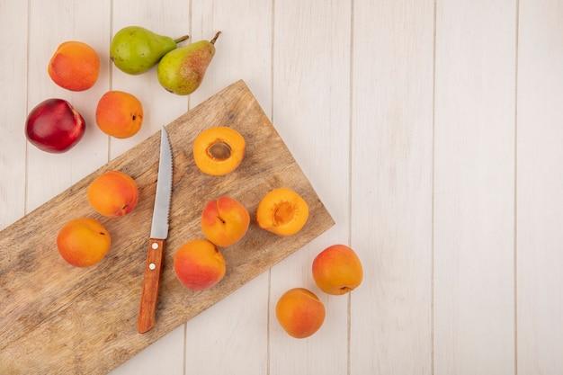 Вид сверху на половину и целые абрикосы и нож на разделочной доске с рисунком фруктов в виде персика, абрикоса и груши на деревянном фоне с копией пространства