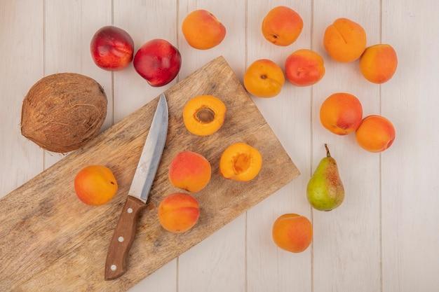 Вид сверху на половину нарезанных и целых абрикосов и нож на разделочной доске с рисунком фруктов в виде персиков, абрикосов, груши и кокоса на деревянном фоне