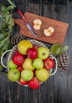 Вид сверху наполовину разрезанного яблока и ножа на разделочной доске с яблочным соком, корзиной яблок, шишки и листьев на деревянном столе