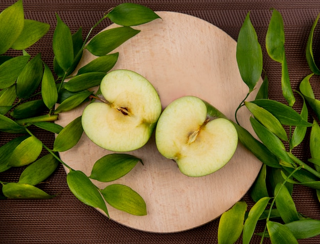 Вид сверху на половину разрезанного яблока с листьями на разделочной доске и на поверхности ткани