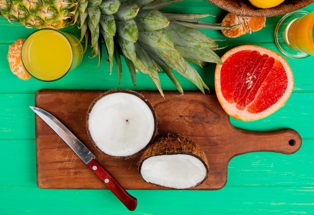 Взгляд сверху половинных кокоса и ножа на разделочной доске с мандарином ананаса грейпфрута и апельсиновым соком на зеленой предпосылке